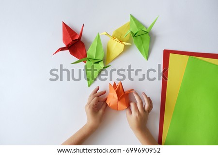 Children's hands do origami from colored paper on white background. lesson of origami #699690952