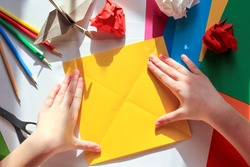 Children's hands doing origami crane from yellow paper on white background with various school supplies. Step-by-step tutorial of origami. Step 4. Concept of children's creativity, back to school.