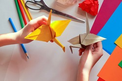 Children's hands doing origami crane from yellow paper on white background with various school supplies. Step-by-step tutorial of origami. Step 18. Concept of children's creativity, back to school.