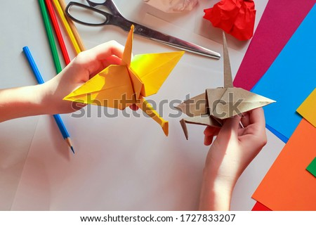 Children's hands doing origami crane from yellow paper on white background with various school supplies. Step-by-step tutorial of origami. Step 18. Concept of children's creativity, back to school. Zdjęcia stock ©