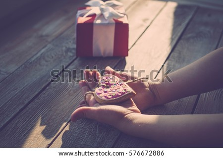 Children's hands hold cookies in the form of heart on a wooden table-top. Sunlight. A concept by the Mother's Day. Vintage toning.