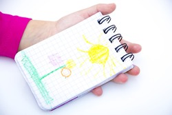 children's hands hold notebook with a painted sun. isolated.