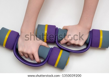 children's hands hold two dumbbells. dumbbells are covered with a soft cloth. White background