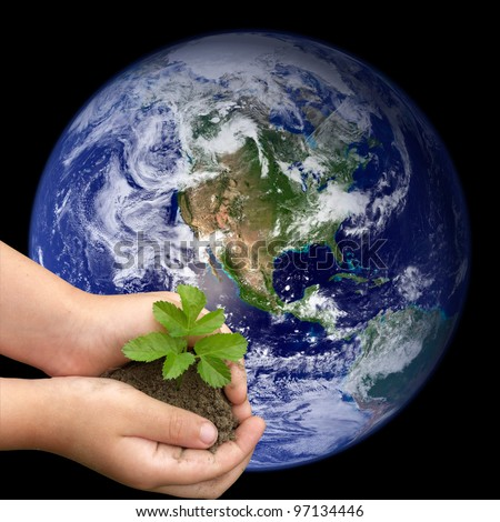 Children\'s hands holding small plant growing from soil on the background of the world. Elements of this image furnished by NASA