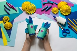 Children's hands make a parrot of colored paper. Toy origami bird. Glue, scissors and paper on a white background. Children's art project for children. Craft favorite.