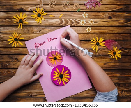 Children's hands make a postcard to her mother in honor of the holiday on the 8th of March. Child creativity, handmade. Dear Mom. Ikebana. #1033456036