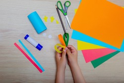 children's hands next to scissors and colored paper and glue. Creativity of children