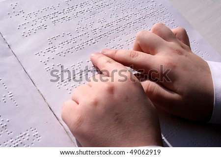 Children's hands on the book read Braille.