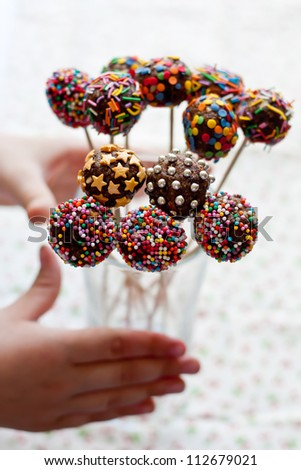 Children's hands reach for a candy on a stick