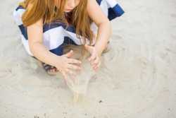 children's hands scattering sand close-up. partially visible is a girl with long blonde hair who throws light sand