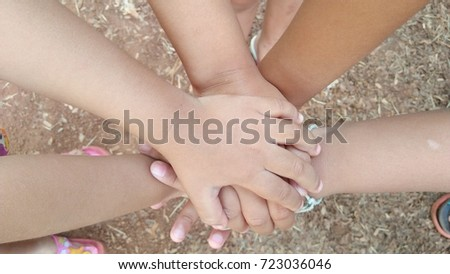 Children's hands stacked to unity.