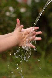 Children's hands under a jet of water