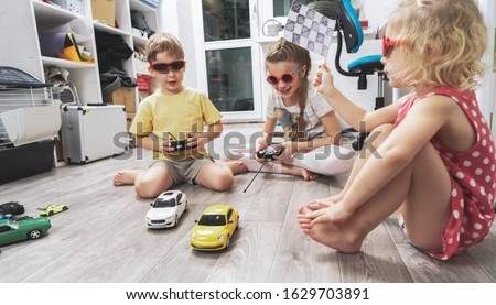 Children's hobbies: Children play at home with radio-controlled models of cars and organized racing competitions. Stock photo ©