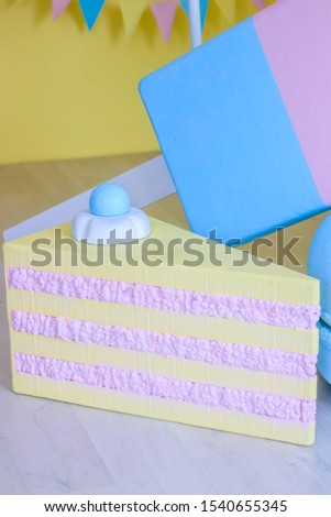 Children's holiday decoration. Holiday decoration. Sweet decorations on yellow background. Big sweets are decorative in the Studio.