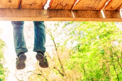 Children's legs hang from the bridge on a background of greenery