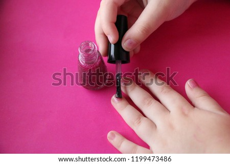 children's manicure. children's hands paint their nails with pink shiny nail polish.  glamorous pink manicure on childish nails with sparkles and rhinestones. #1199473486