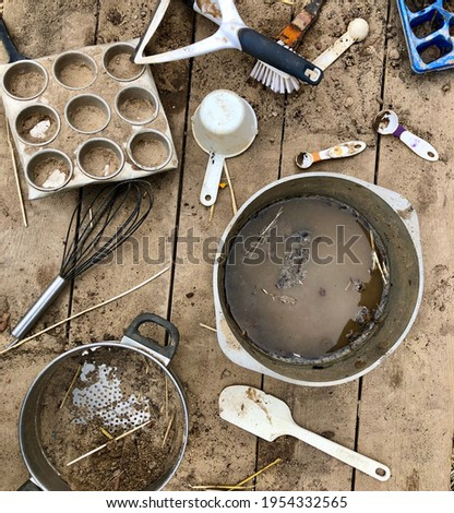 Children's outdoor mud kitchen at a preschool. Pots, pans, utensils cover with mud, dirt and sand. Stock photo ©