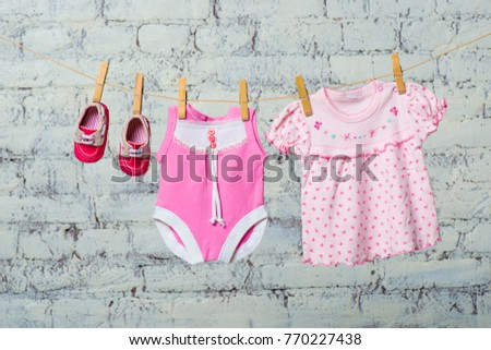 Children's pink bodic, dress and red shoes for the girl, dry on a rope against a white brick wall. #770227438