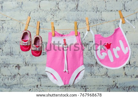 Children's pink body, bib and red shoes, dry on a rope against a white brick wall. #767968678
