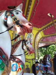 Children's plastic carousels in the form of a horse in an amusement park. Summer family vacation.