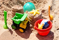Children's plastic toys green end yellow car, shovel, red bucket, green ball with yellow sand on the beach by sea. Children's beach toys on sand on a sunny day. Sandbox on the playground for games