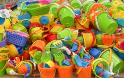 Children's plastic toys. New toy bucket, blade, rake, cars in the store. Sale of children's products.