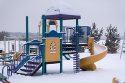 Children's playground covered with snow in winter