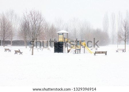 Children's playground covered with snow in winter, Milano, Italy