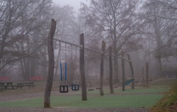 Children's playground in foggy and cold day