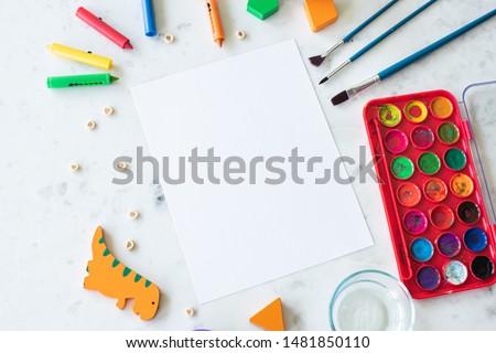 Children's Preschool Art Supplies surrounding Blank Paper Mockup Concept Flat Lay for Montessori Class Foto stock ©