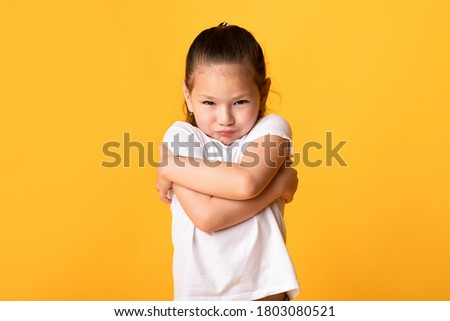 Children's Protest. Upset little female pupil holding arms crossed on yellow background, free space Stock foto ©