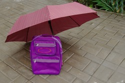 Children's purple school backpack or briefcase stands on tiles under a crimson umbrella.