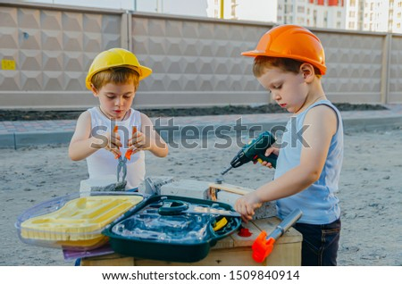 Children's role-playing games - a profession builder. Early development of the child, ideas for the game. A team of builders with tools at a construction site. Fun time with friends #1509840914