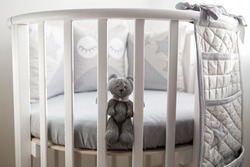 children's round white bed with sitting toy rabbit
