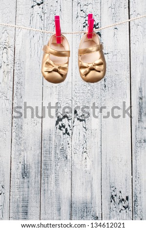 Children's sandals hanging on a clothesline.