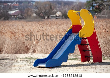 children's slide located in a deserted place. dried grass field. empty playground. sunny day. Foto stock ©
