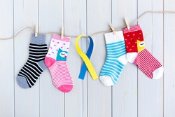 Children's socks with stripes and colors in clothesline on wooden background. In the center there is a yellow and blue ribbon. World Down Syndrome Day concept.