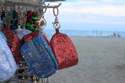 children's souvenir bags on the background of the beach and sea. A souvenir from a seaside holiday. Tourist children's souvenir