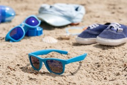 Children's sunglasses on a baked beach. Kids toys. Summer holiday concept
