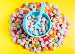 Children's tableware silicone bowl with spoon. Serving baby food, kid dishware.blue silicone bowl and spoon are in a heap of sweets and marmalade. bright, colorful photo flatly