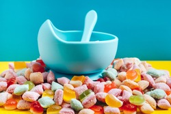 Children's tableware silicone bowl with spoon. Serving baby food, kid dishware.blue silicone bowl and spoon are in a heap of sweets and marmalade. bright, colorful photo