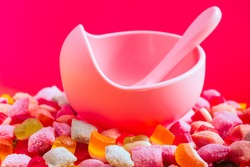 Children's tableware silicone bowl with spoon. Serving baby food, kid dishware.Pink silicone bowl and spoon are in a heap of sweets and marmalade. bright, colorful photo