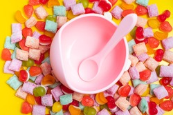 Children's tableware silicone bowl with spoon. Serving baby food, kid dishware.Pink silicone bowl and spoon are in a heap of sweets and marmalade. bright, colorful photo flatly