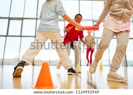 Children's team makes a relay race in physical education in the gym