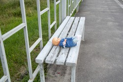 Children's toy doll in dress and pants lies forgotten on a wooden bench