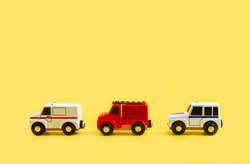 Children's toy, three cars on a yellow background. Police car, fire truck, ambulance. Emergency. Concept. Isolate. High quality photo