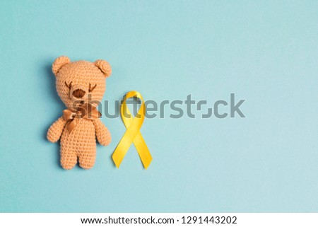 Children's toy with a Childhood Cancer Awareness Yellow Ribbon on blue background. Childhood Cancer Day February, 15.