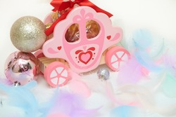 Children's toy wooden carriage toy with Christmas tree decorations, decoration red bow and soft colored feathers. Gift for kids and lovers isolated on white background. Copy space