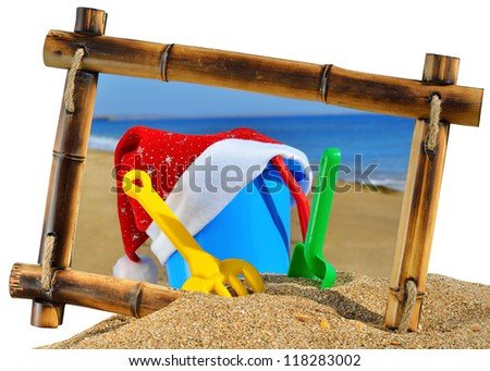 Children's toys and Santa's hat  in bamboo frame on the beach against a blue ocean isolated on white background