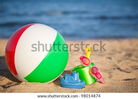 Children`s toys for sand and inflatable ball at the beach. Summer vacations concept